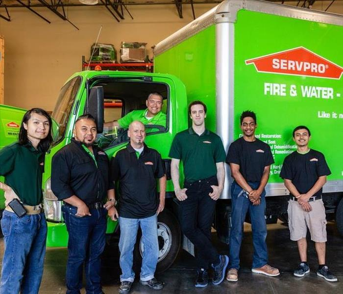 A group of SERVPRO workers standing in front of a truck.