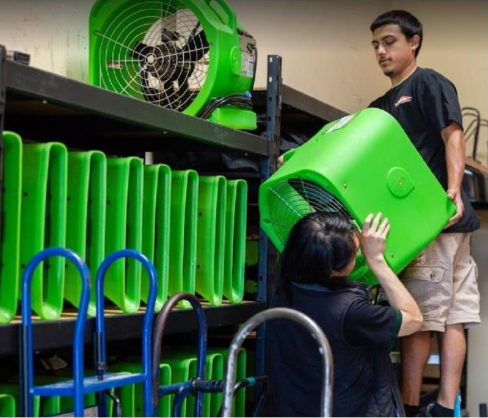 SERVPRO technicians stacking restoration equipment in storage facility