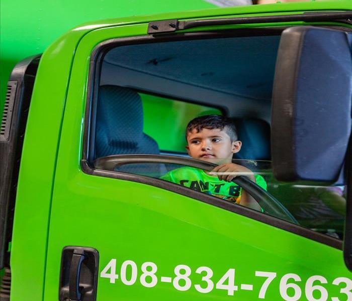 young boy sitting in a SERVPRO truck